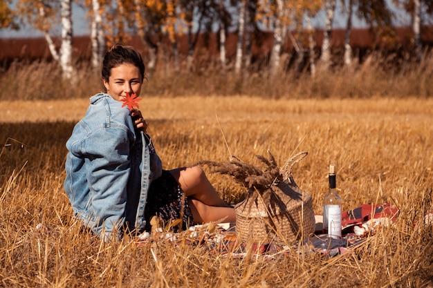 Piknik na świeżym powietrzu: młoda kobieta w dżinsowej kurtce i sukience trzyma czerwony liść i cieszy się przyrodą, siedząc na kratce z koszem piknikowym, jabłkami, winem.
