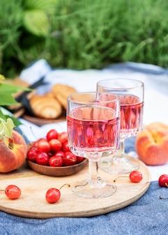 Piknik na świeżym powietrzu na polach lawendy. wino różowe w kieliszku, wiśnie i słomkowy kapelusz na kocu