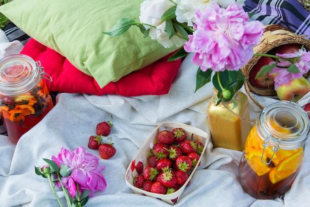 Piknik na świeżym powietrzu z truskawkami i zimnymi napojami