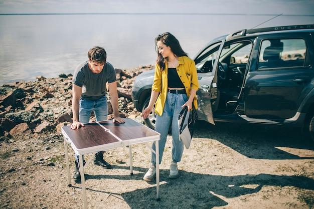 Piknik nad wodą. szczęśliwa rodzina na wycieczce samochodem. mężczyzna i kobieta podróżują nad morzem, oceanem lub rzeką. letnia przejażdżka samochodem.