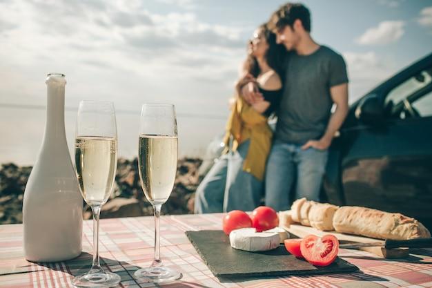 Piknik nad wodą. szczęśliwa rodzina na wycieczkę samochodową. luźna bagietka, pomidory z białego sera i szampana.