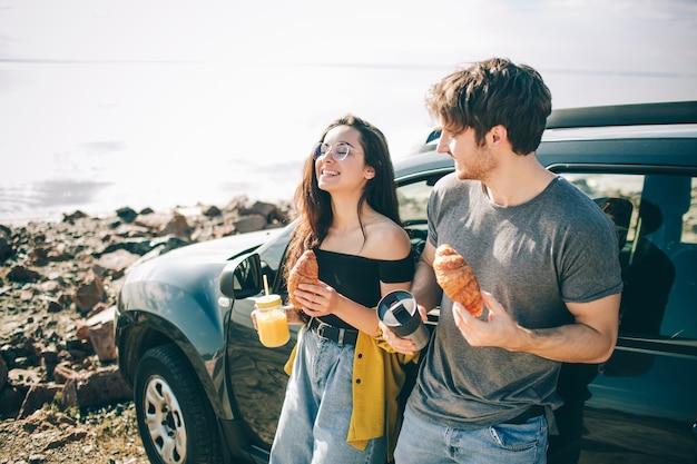 Piknik nad wodą. szczęśliwa rodzina na wycieczkę samochodową. mężczyzna i kobieta podróżują morzem, oceanem lub rzeką. letnia jazda samochodem. zatrzymali się na przekąskę.