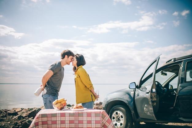 Piknik nad wodą. szczęśliwa rodzina na wycieczkę samochodową. mężczyzna i kobieta podróżują morzem, oceanem lub rzeką. letnia jazda samochodem.