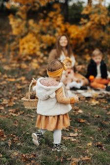 Piknik rodzinny w jesiennym parku. powrót z małą dziewczynką trzyma kosz. matka, siostra i brat w tle.