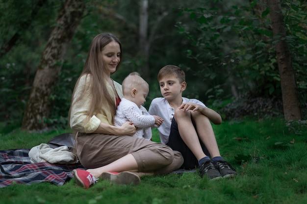 Piknik rodzinny w ogrodzie parku na świeżym powietrzu. matka, najstarszy syn i najmłodsze dziecko siedzi na kocu piknikowym