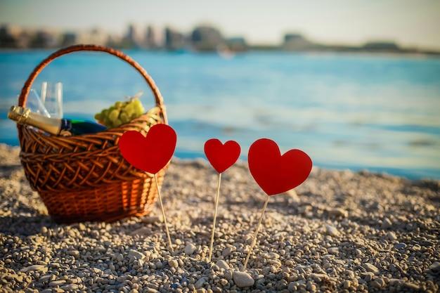 Piknik. szampan. koszyk piknikowy. piękna morska plaża. serca na plaży stoją na patykach. walentynki