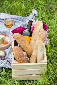 Piknik w parku na trawie: wino, sery i pieczywo