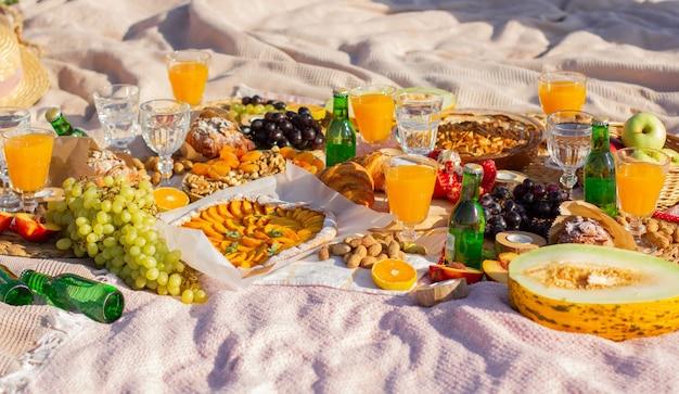 Piknik w parku z pięknymi kieliszkami, owocami i ciastami.
