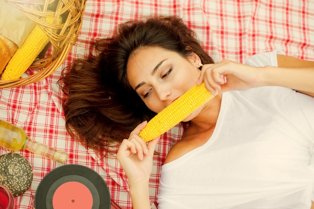 Piknik w stylu retro. młoda wesoła blondynka w strojach vintage je kukurydzę, leżąc na obrusie piknikowym na świeżym powietrzu