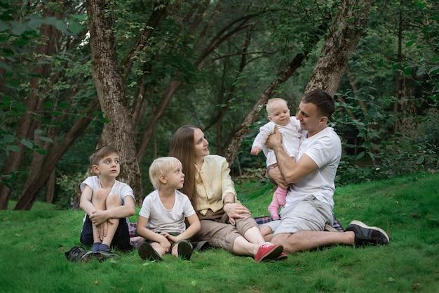 Piknik z całą rodziną. przyjazna kochająca rodzina. rodzice i troje dzieci.