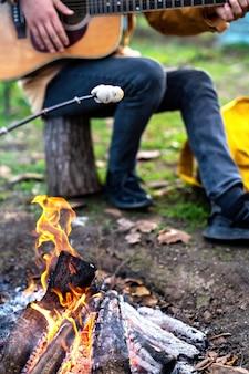 Piknik z ogniskiem, jeden mężczyzna gra na gitarze, inny na ogniu gotuje pianki