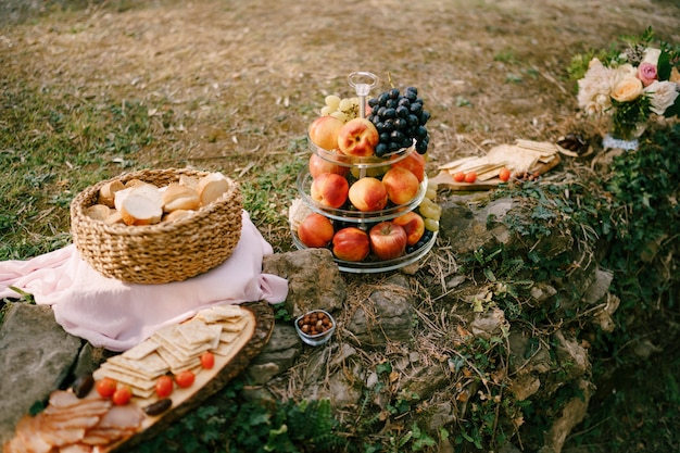 Piknik z owocami, koszyczek z kromkami chleba oraz deska z serami i kawałkami mięsa na kamieniach