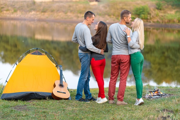 Piknik z przyjaciółmi nad jeziorem w pobliżu namiotu kempingowego. firma przyjaciele ma podwyżki natury pyknicznego tło. turystów relaks w czasie picia. letni piknik. zabawa z przyjaciółmi.