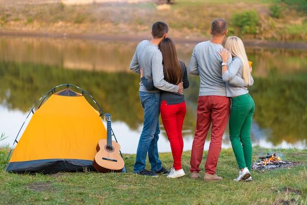 Piknik z przyjaciółmi nad jeziorem w pobliżu namiotu kempingowego. firma przyjaciele ma podwyżki natury pyknicznego tło