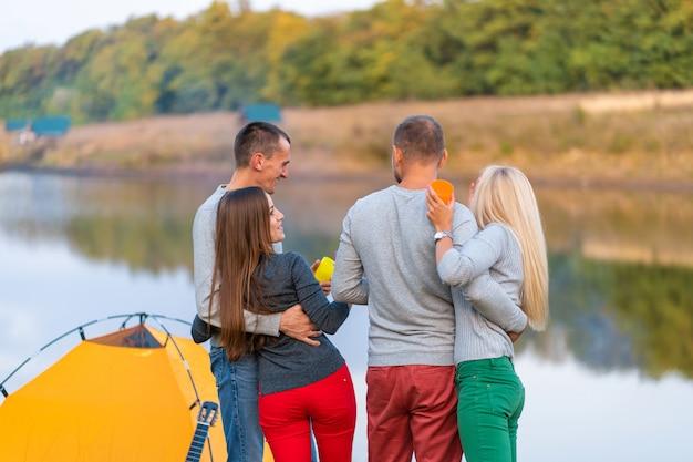 Piknik z przyjaciółmi nad jeziorem w pobliżu namiotu kempingowego. przyjaciele o wycieczkę charakter piknik