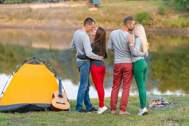 Piknik z przyjaciółmi nad jeziorem w pobliżu namiotu kempingowego