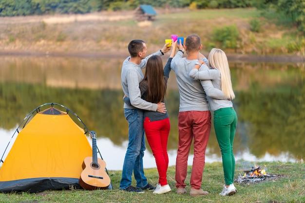 Piknik z przyjaciółmi przy jeziorze w pobliżu namiotu kempingowego, przyjaciele firmy o wycieczce na tle przyrody piknikowej, wycieczkowicze relaksujące podczas drinka, letni piknik, czas zabawy z przyjaciółmi.