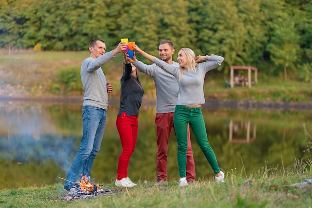 Piknik z przyjaciółmi przy jeziorze w pobliżu ogniska. firma przyjaciele ma podwyżki natury pyknicznego tło. turystów relaks w czasie picia. letni piknik. zabawa z przyjaciółmi