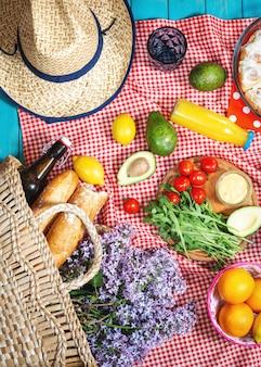 Piknik ze świeżymi owocami, warzywami, sałatką, sokiem pomarańczowym i bagietką