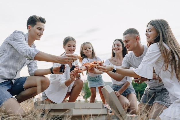Piknikowi przyjaciele z pizzą i napojami piją i jedzą na zdrowie, słoneczny dzień, zachód słońca, towarzystwo, zabawa, pary i mama z dzieckiem
