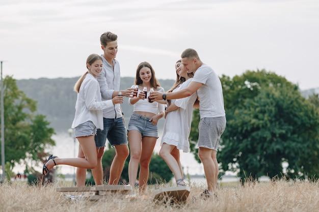 Piknikowi przyjaciele z pizzą i napojami piją i jedzą z okrzykami, słoneczny dzień, zachód słońca, towarzystwo, zabawa, pary i mama z dzieckiem