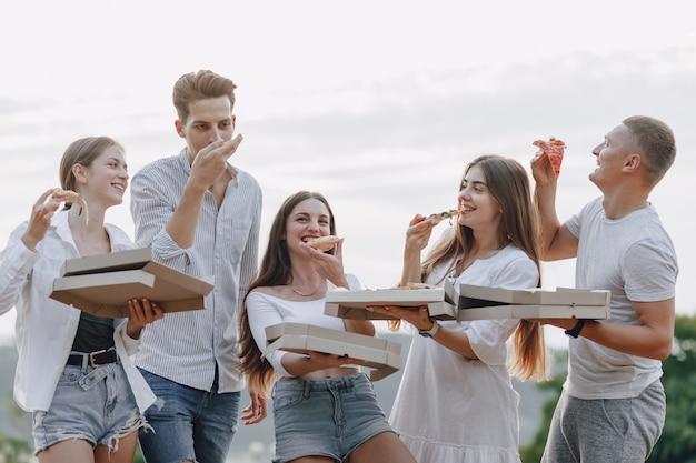 Piknikowi przyjaciele z pizzą i napojami, słoneczny dzień, zachód słońca, towarzystwo, zabawa, pary i mama z dzieckiem