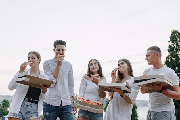 Piknikowi przyjaciele z pizzą i napojami w słoneczny dzień