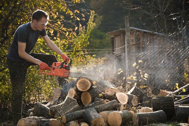 Piła łańcuchowa, która stoi na stercie drewna opałowego na podwórku na pięknej zielonej trawie i lesie. cięcie drewna za pomocą testera silnika