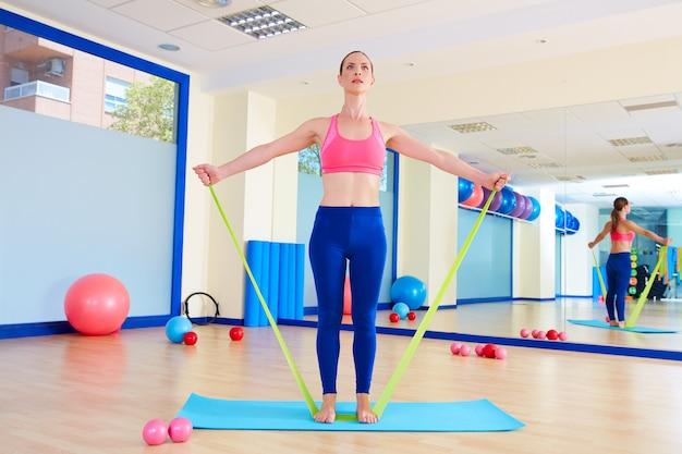 Pilates kobieta stojąca gumka ćwiczenia