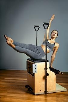 Pilates reformatora krzesło kobieta fitness joga siłownia ćwiczenia. korekta układu mięśniowo-szkieletowego, piękne ciało. prawidłowa postawa