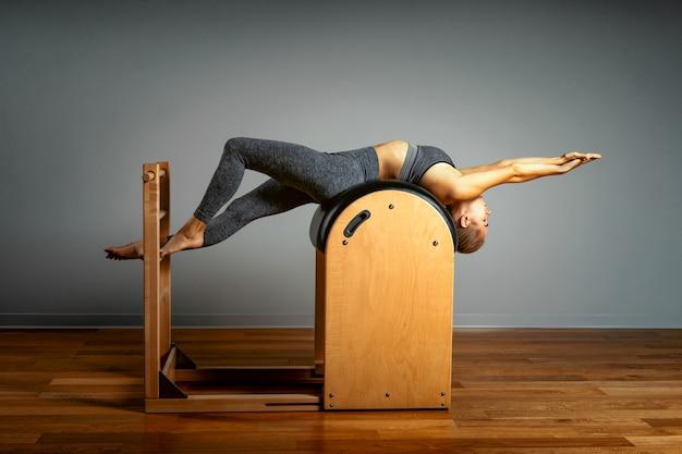 Pilates, sprawność fizyczna, sport, szkolenie i ludzie pojęć, - kobieta robi ćwiczeniom na małej baryłce. korekta impulsu aparatu, prawidłowa postawa.