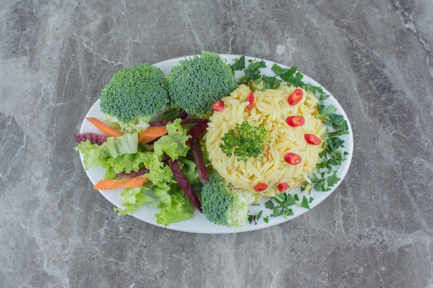 Pilau na talerzu z marmuru przyozdobionym posiekaną papryką, kapustą, zieleniną, marchewką i kawałkami brokułów.