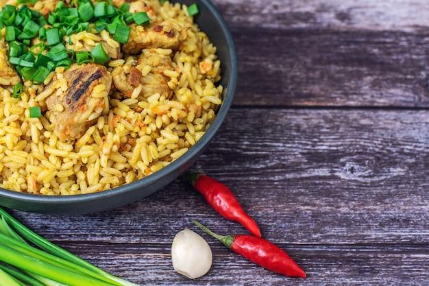 Pilaw ryżowy z mięsną marchewką i cebulą na drewnie.