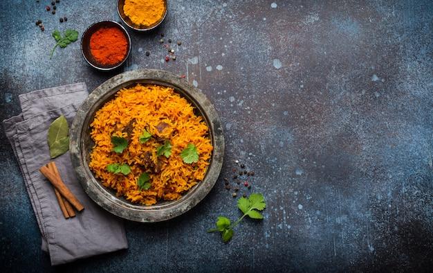 Pilaw - tradycyjne wschodnie danie z ryżem, warzywami i mięsem podawane na vintage talerzu ze świeżą kolendrą, sosami i przyprawami na rustykalnym tle, widok z góry i miejsce na tekst