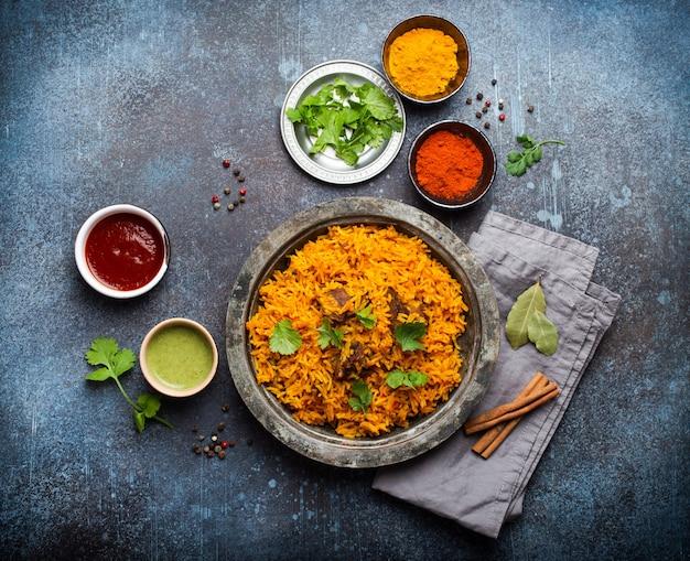 Pilaw - tradycyjne wschodnio-azjatyckie danie z ryżem, warzywami i mięsem podawane na vintage talerzu ze świeżą kolendrą, sosami i przyprawami na rustykalnym tle, widok z góry, zbliżenie