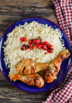 Pilaw w talerzu z mięsem z kurczaka, żurawiną na ręczniku drewnianym i kuchennym