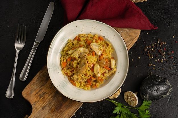 Pilaw z kurczakiem i marchewką. tradycyjne gorące danie z ryżu uzbeckiego mięsa z kurczaka i warzyw ozdobione pietruszką i czosnkiem na czarnym stole, widok z góry.