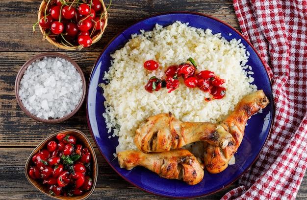 Pilaw z mięsem z kurczaka, wiśnią, solą w talerzu na ręczniku drewnianym i kuchennym.
