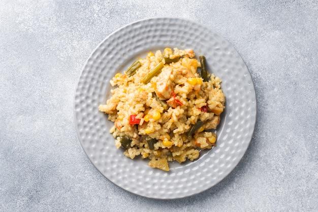 Pilaw z warzywami i kurczakiem w szarym talerzu