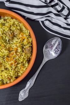 Pilaw z wołowiną, marchewką, cebulą, czosnkiem, papryką i kminkiem. tradycyjne danie kuchni azjatyckiej. selektywne skupienie