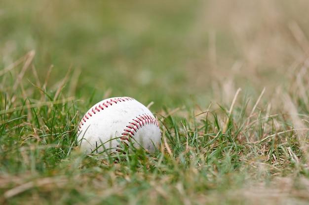 Piłka baseballowa leżąca na ziemi sportowej koncepcji