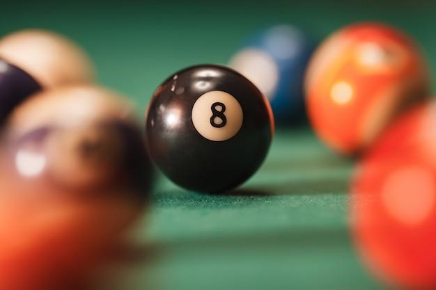 Piłka bilardowa z numerem 8 na zielonym tle.