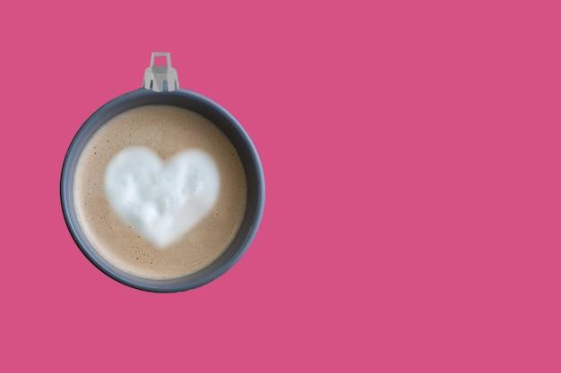 Piłka choinkowa wykonana z filiżanki kawy w różowym tle