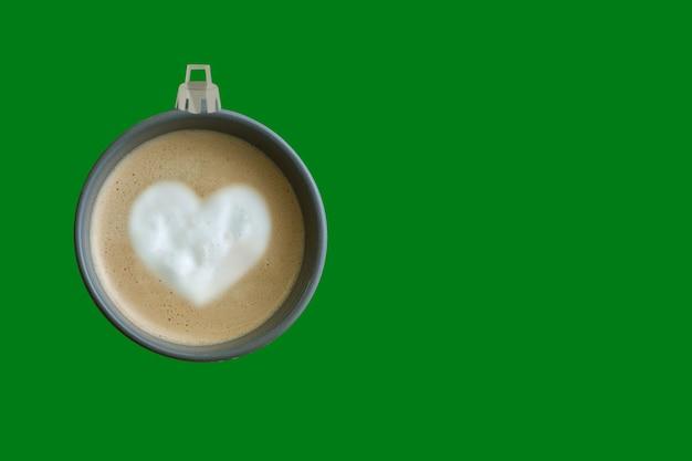 Piłka choinkowa wykonana z filiżanki kawy w zielonym tle