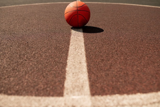 Piłka do gry w koszykówkę leżąca pośrodku pionowej białej linii na nowoczesnym stadionie lub boisku