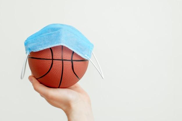 Piłka do koszykówki z maską medyczną.
