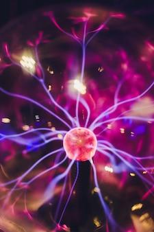 Piłka dotykowa plazmy z gładkimi purpurowo-niebieskimi płomieniami.