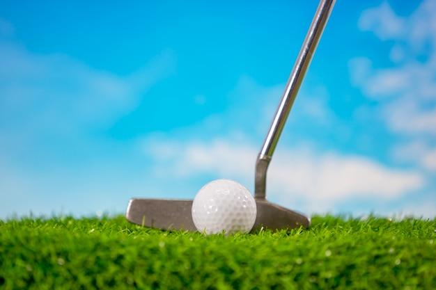 Piłka golfowa i kij golfowy dla stawiać na niebieskim niebie