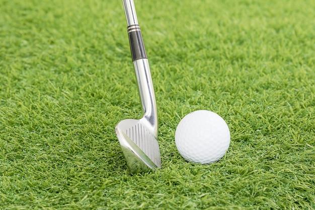 Piłka golfowa i klub golfowy na zielonej trawie