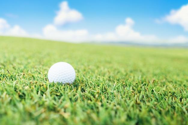 Piłka golfowa na trawie i niebie